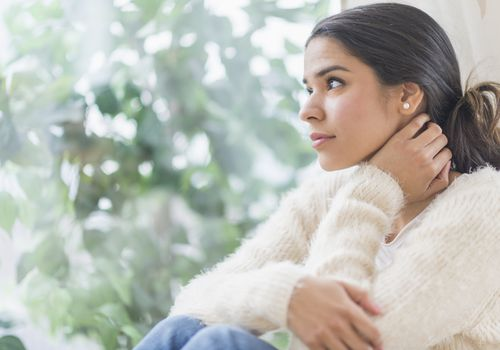 Woman looking out window, feeling depressed and not sure what to do