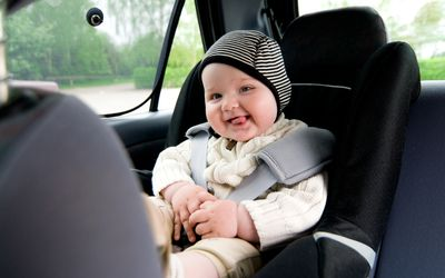 Baby wearing hat and sweater smiling in car seat.
