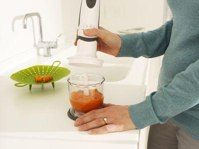Woman preparing baby food using blender, close-up