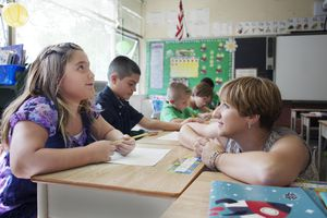 Teacher Listening to her Student in the Classroom