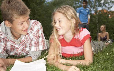A boy and a girl reading a magazine in a park
