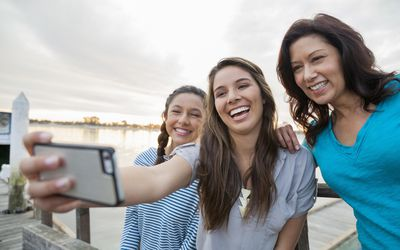 Two teenage girls taking a selfie with their mother outdoors