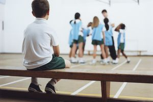 Kids in gym class - one boy sitting on bench