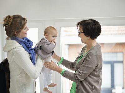 mom handing infant over to babysitter