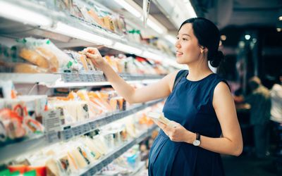 Pregnant woman shopping for cheese