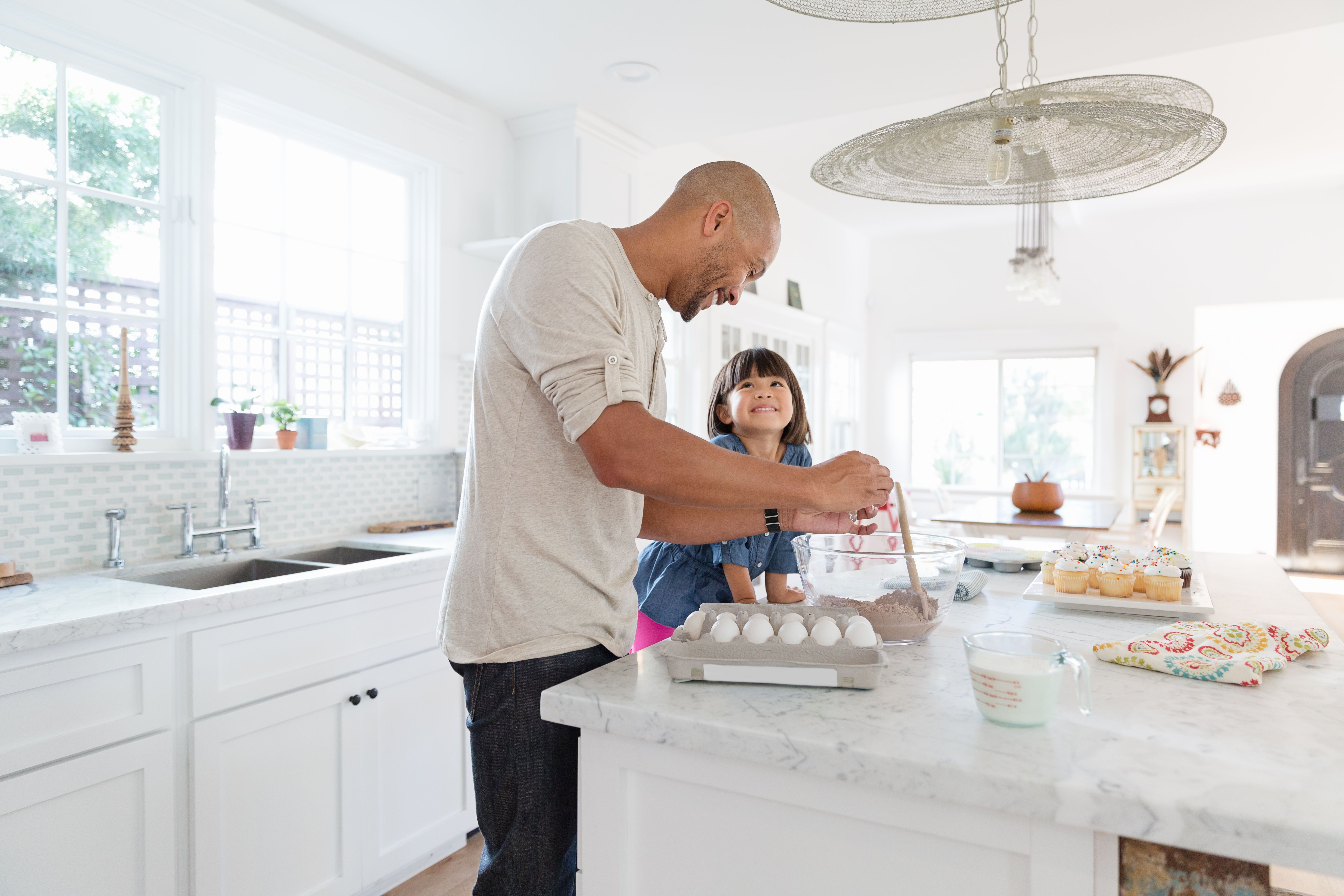 Father and toddler daughter baking cupcakes in kitchen