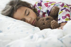 girl sleeping in bed with teddy bear