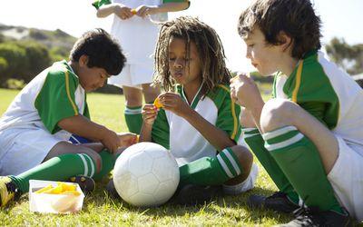 boys eating orange slices at halftime during soccer game