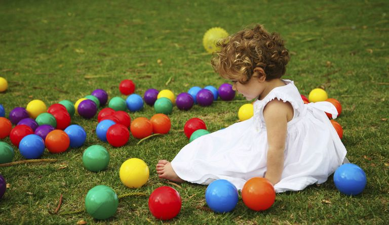 Little girl with colorful plastic toy balls