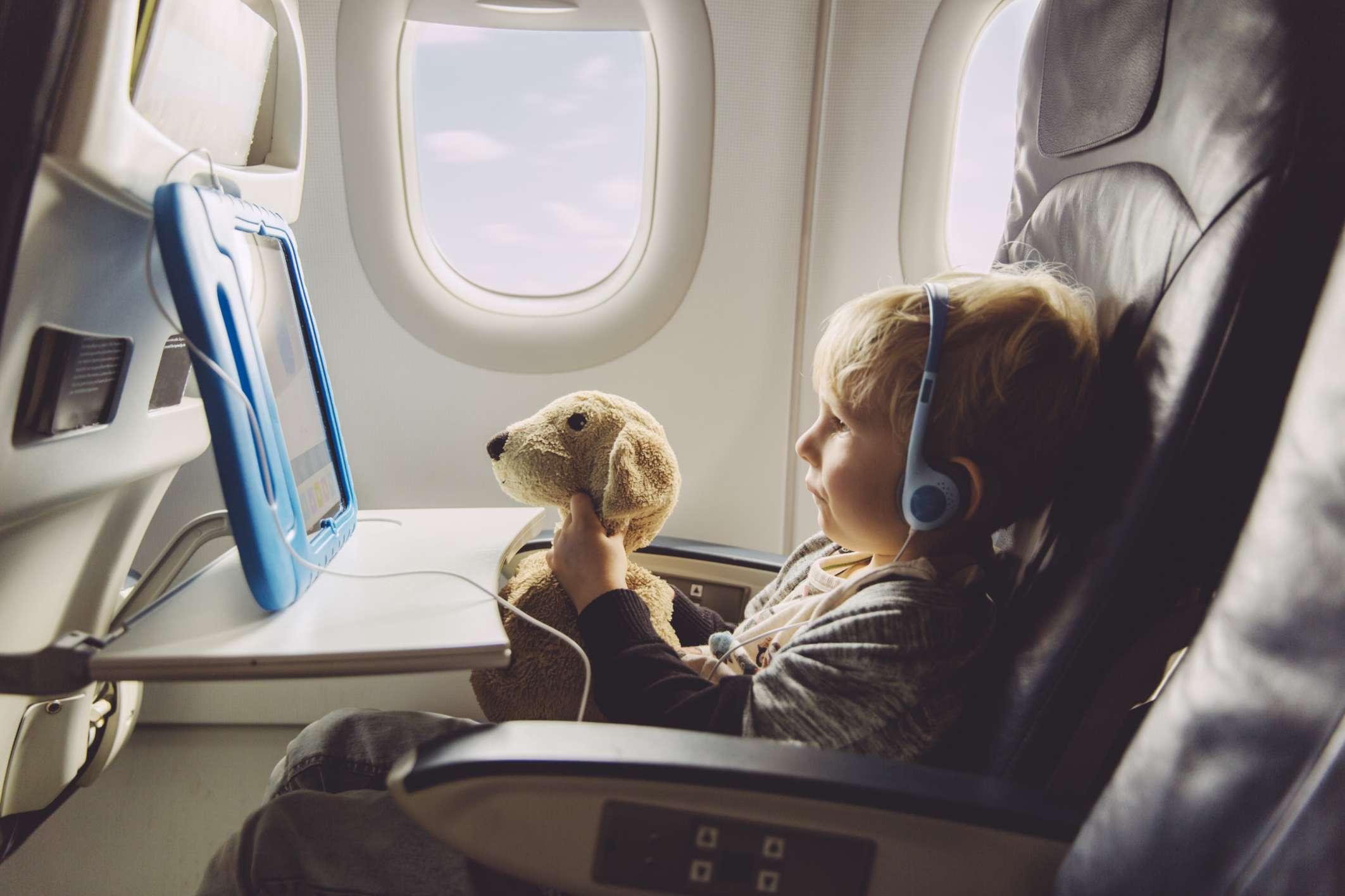 Little boy watching movie on plane with stuffed animal