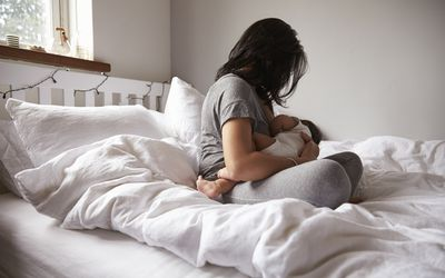 Woman breastfeeding baby in bed