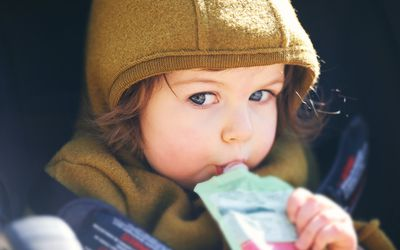 Close up portrait of sweet toddler kid eating fruit puree from plastic doy pack, sitting in stroller, outdoor snack time