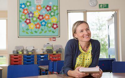teacher smiling at desk