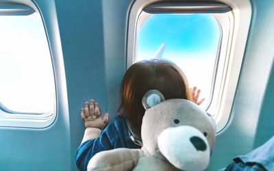 Toddler looking out airplane window
