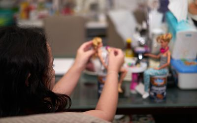 girl playing with Barbie dolls
