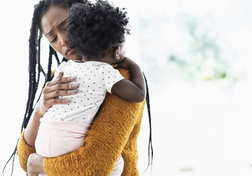 Black woman holding and comforting baby daughter