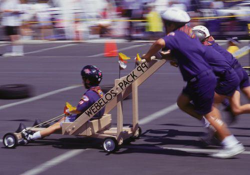 Webelos having downhill cart race.