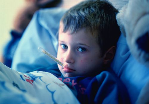 Young boy (3-5) in bed with thermometer in mouth
