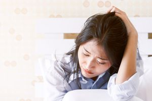 Upset woman holding her head in bed