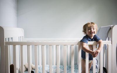 Toddler boy smiling in crib, close-up