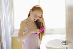 Girl brushing long hair in bathroom