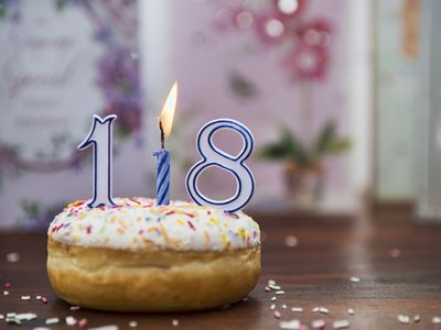 iced donut with candles spelling out the number 18