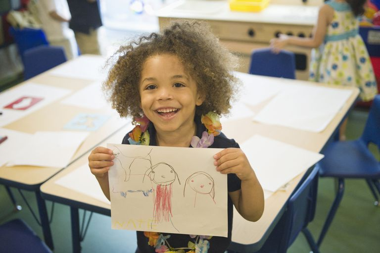 Cute boy shows off picture he drew.