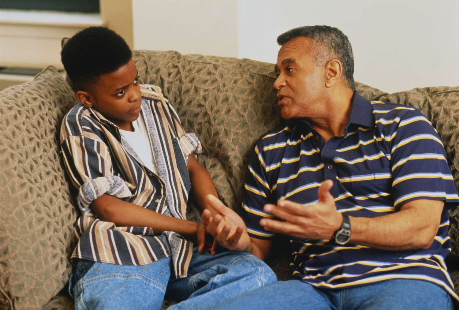 Father talking seriously to teenage son (11-13), sitting on couch