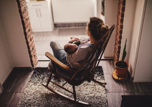Photo of a young mother holding her newborn baby, while sitting in a rocking chair