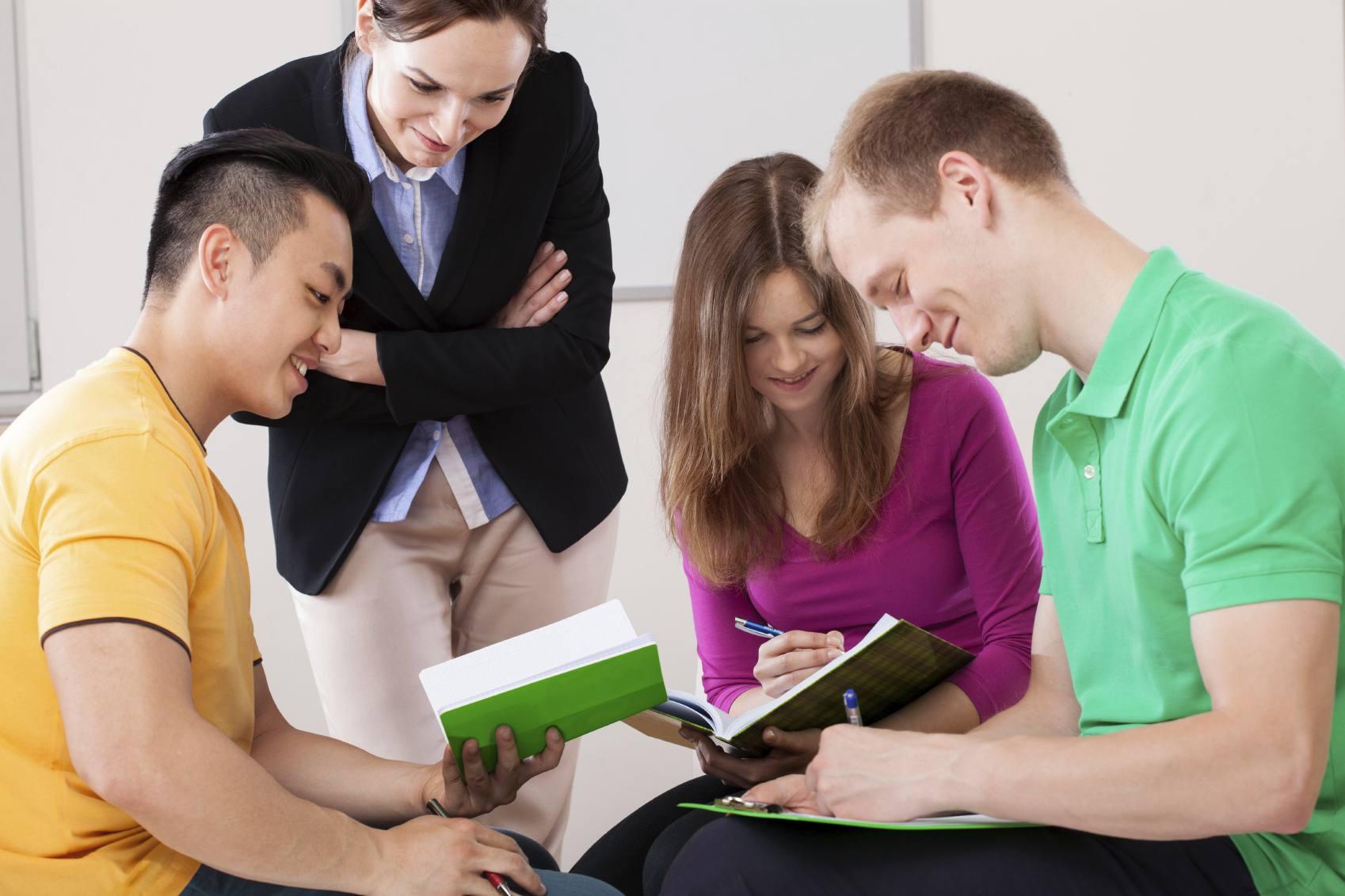 Teacher looking over shoulders of students