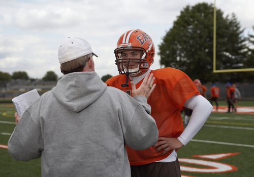 High school football player speaking with coach