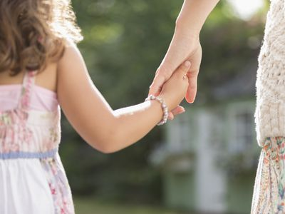 mother and young daughter holding hands