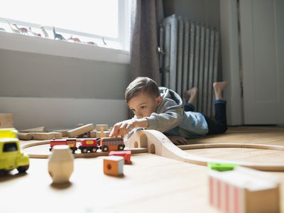 Boy playing with toy train on floor