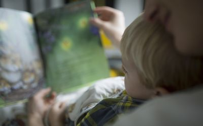 Child looking at picture book with mom