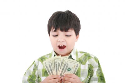 Boy with brown hair holds a stack of money and looks surprised