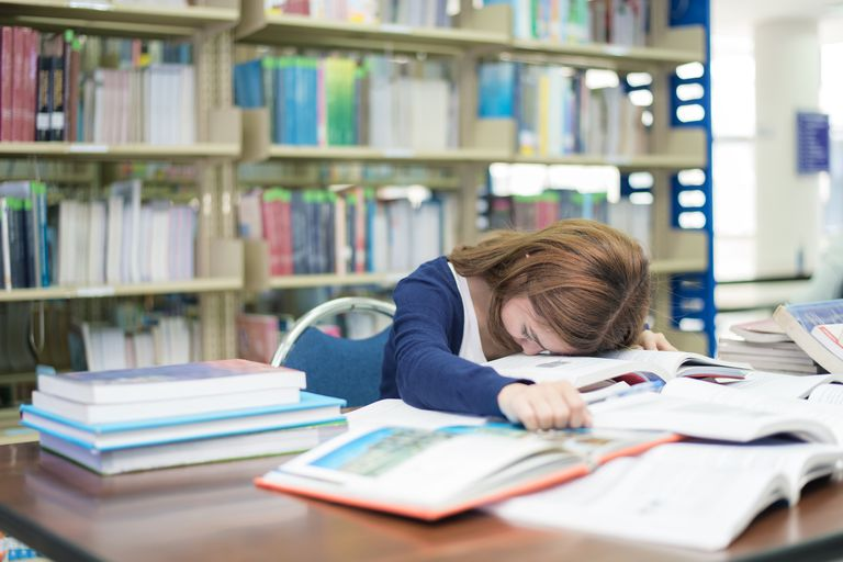 Tired student or young woman with many books sleeping while reading book prepare examination in library at university. People, education, session, exams and school concept