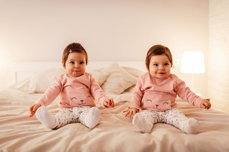 twin toddlers in matching outfits sitting on a bed
