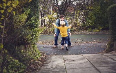 a little boy running into his father's arms