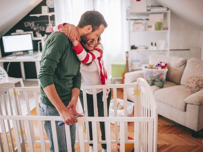 expecting father helping wife build crib for baby