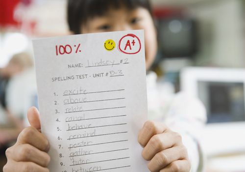 child holding up a spelling test with a grade of 100.
