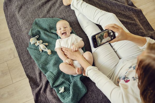 A mother takes a video of a baby with a smartphone. The baby is laying on a green blanket and is wearing a white onesie. There are toys scattered around.