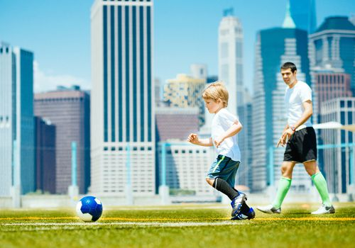 child playing soccer with coach and cityscape in background