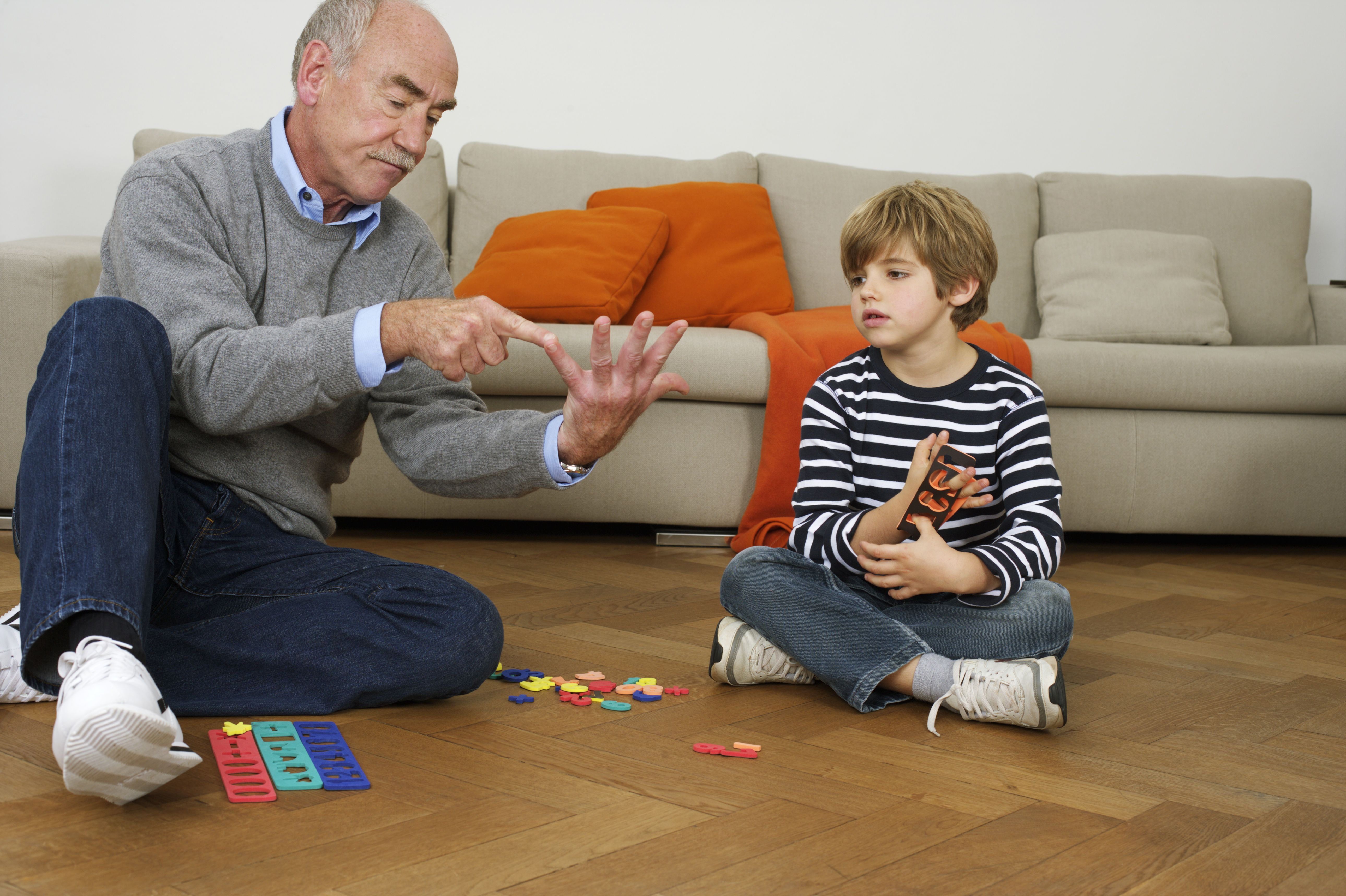 Grandfather and grandson (6 years) playing on floor