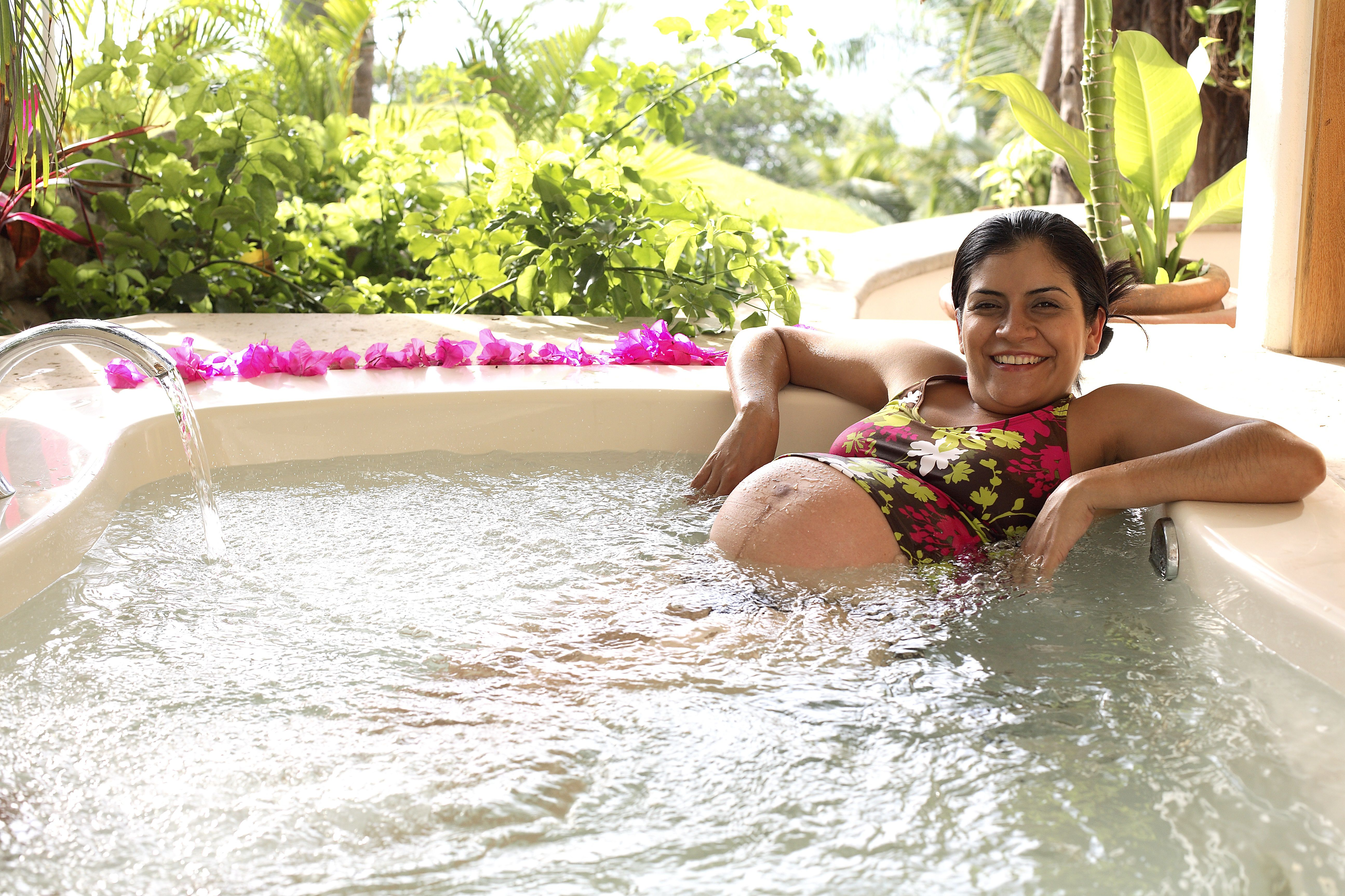 Pregnant woman smiling in hot tub