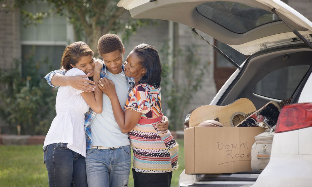 Family hugging teenage boy as he prepares for college