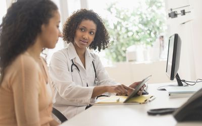 Doctor talking with a woman about the possible risk of cancer after fertility drugs and infertility