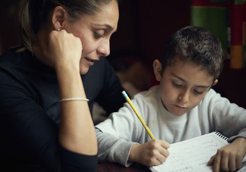 A mother sit next to her child and helps him with homework.