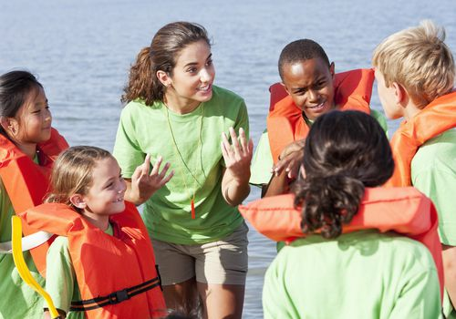 Summer camp counselor talking to children wearing life jackets