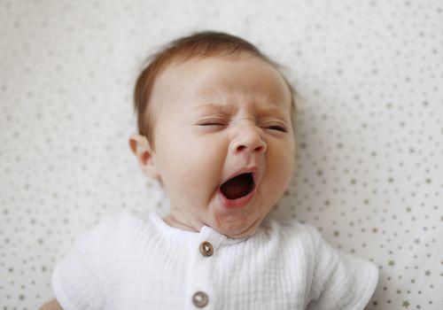 A baby yawning in crib.