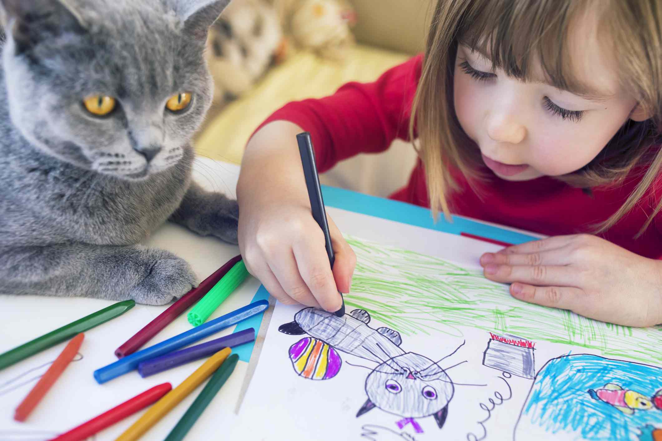 Child with kitty drawing at home